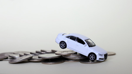 A white miniature car on the coins.
