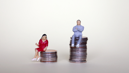 Concept of difference between pay men and women. A miniature man and a woman sitting on a pile of coins.