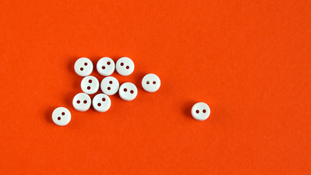 Ten white buttons and a white button. Stock Photo