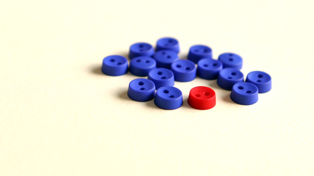 Several blue buttons and a red button between them. Stock Photo