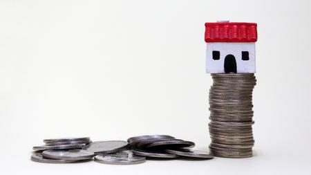 Varias monedas y una casa en miniatura sobre una pila de monedas. Foto de archivo - 98233796