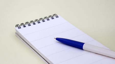 Wire bound notebook pad and ballpoint on soft yellow background.