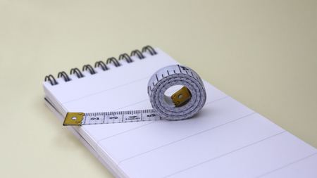 A tape measure on a wire bound notebook pad. Stock Photo