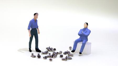 A miniature man standing and a sitting miniature man.