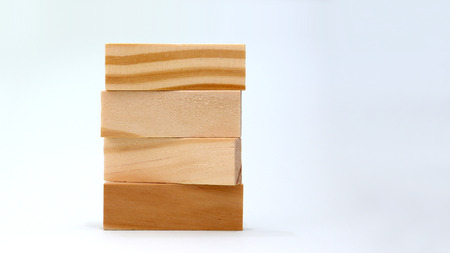 A pile of four wooden blocks on a soft gray background. Stockfoto
