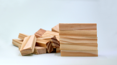 A pile of five wooden blocks in front of stacked blocks of wood. Stockfoto