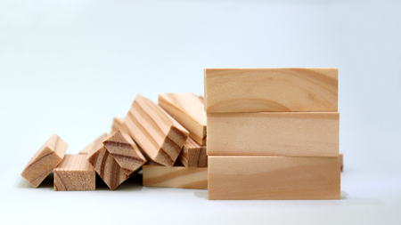A pile of three wooden blocks in front of stacked blocks of wood.
