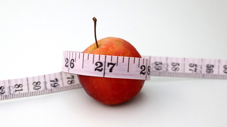 A tape measure covering an apple. Stock Photo