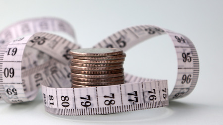 A tape measure of coins wrapped around a pile.