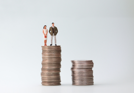 A pile of coins and a miniature people standing on a pile of coins. Stock Photo