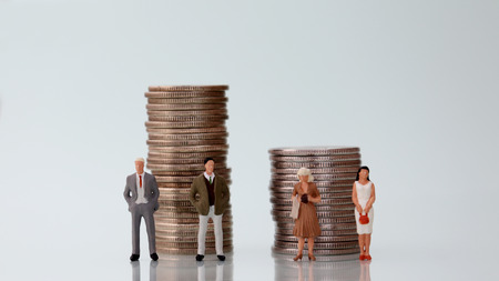 The concept of gender pay discrimination. Miniature men and women standing next to a pile of coins of different heights.