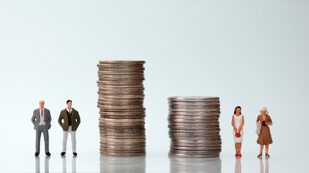 The concept of gender pay discrimination. Two piles of coins and four miniature people.