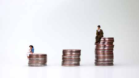 The concept of gender inequality. A miniature man is sitting on a pile of coins.