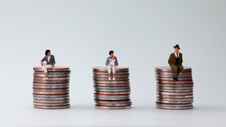 The concept of equal share. Miniature women holding baby sitting on a pile of coins.