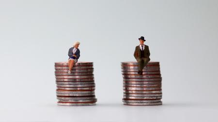 El concepto de participación equitativa. Un hombre en miniatura y una mujer en miniatura sentada sobre una pila de monedas de igual altura. Foto de archivo