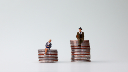 Gender wage differentials in the workplace concept. A miniature man and a miniature woman sitting on a pile of coins at different heights. Stock Photo