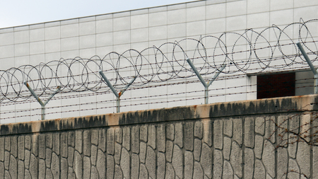 Barbed wire entanglement on a wall. Stock Photo