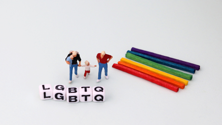 Dice word LGBTQ on soft white background. The concept of changing the social perception of the same gender couples and families.