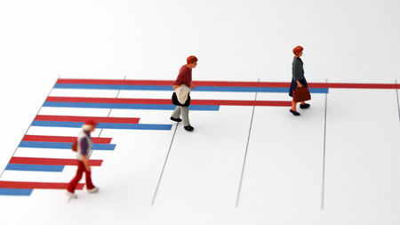 Social statistics and peoples concepts. Miniature people standing on a bar graph.