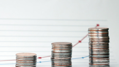 Linear graph and three piles of coins. The deepening concept of the wealth gap. Stock Photo