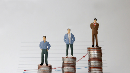 Miniature people standing on a pile of graphs and coins on a white background. The concept of social income gap.