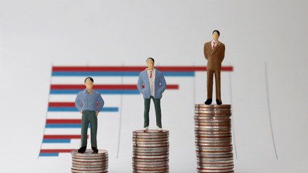 Miniature people standing on a pile of graphs and coins on a white background. The concept of a widening wealth gap.