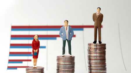 Miniature people standing on a pile of graphs and coins on a white background. The concept of social income inequality.