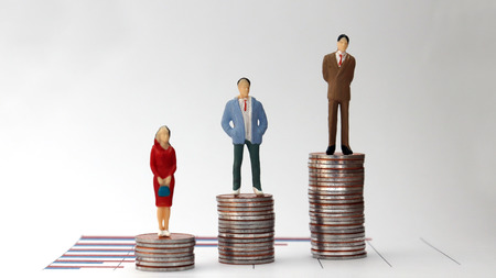 Miniature people standing on a pile of graphs and coins on a white background. A concept of economic inequality. Stock Photo