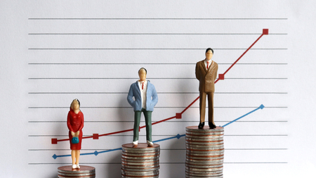 Miniature people standing on a pile of graphs and coins on a white background. The idea of ??a growing income gap. Stock Photo