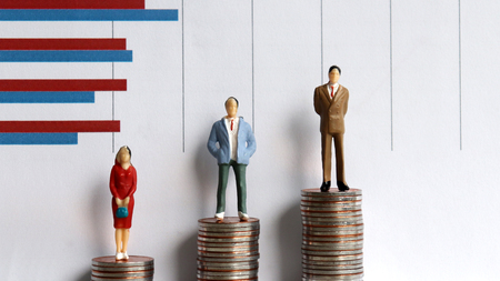 Miniaturleute, die auf einem Stapel von Münzen vor einem Diagramm stehen. Income Gap Disparity-Konzept.