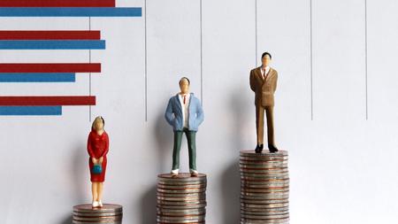 Persone in miniatura in piedi su una pila di monete davanti a un grafico. Concetto di disparità del divario di reddito.