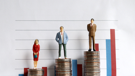 Miniature people standing on a pile of coins in front of a graph. The concept of the relationship between the occupation and the income gap.