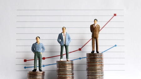 Miniature people standing on a pile of coins in front of a graph. The concept of the difference between occupation and income. Stockfoto