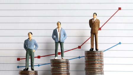 Miniature people standing on a pile of coins in front of a graph. The concept of the difference between occupation and income. Stock Photo