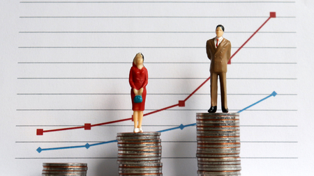 Miniature people standing on a pile of coins in front of a graph. The concept of the growing income gap in the profession.