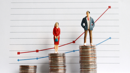 Miniature people standing on a pile of coins in front of a graph. The concept of the wage gap between men and women in the workplace. Stock Photo