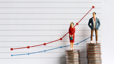 Miniature people standing on a pile of coins in front of a graph. The concepts of continuing gender inequality. Stock Photo