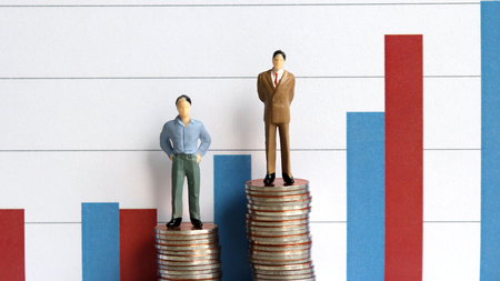 Miniature people standing on a pile of coins in front of a graph. The concept of a continuing income gap imbalance. Stock Photo