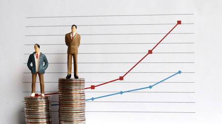 Miniature people standing on a pile of coins in front of a graph. The concept of the widening income gap.