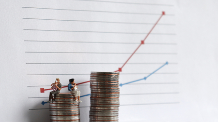 A miniature woman sitting on a pile of coins with a baby in front of a linear graph. The concept of income gap and child care costs.