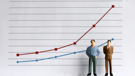 Two miniature men standing in front of a linear graph. The concept of increasing income gap. Stock Photo