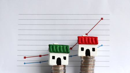 Housing price rising and differentiated concept. A miniature house on a pile of coins in front of a graph. Stockfoto