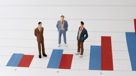 Three miniature men standing on a bar graph.