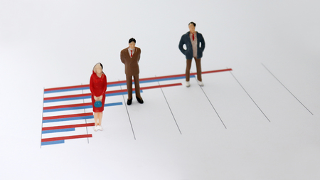 Miniature people standing on a bar graph. Numerical value and peoples relationship concepts.