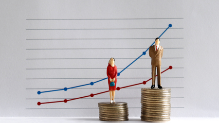 A miniature man and a miniature woman standing on top of a pile of coins at different heights in front of a linear graph. The concept of gender inequality. Stock Photo