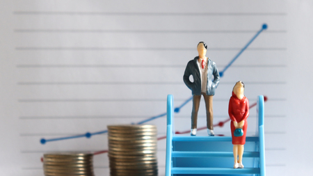 A miniature man and a miniature woman standing on the stairs in front of the graph.