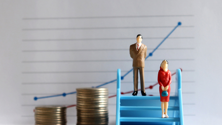 A miniature man and a miniature woman standing on the stairs in front of the graph. Different treatment concepts between men and women at work. Stock Photo
