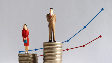 The concept of continuing gender pay gap. A miniature man and a miniature woman standing on top of a pile of coins at different heights in front of a bar graph.