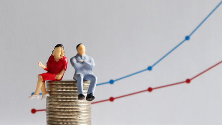 The concept of the wage gap between men and women in the workplace. A miniature man and a miniature woman sitting on a pile of coins in front of a linear graph. Stock Photo