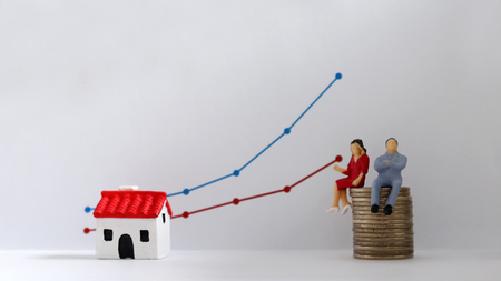A miniature couple sitting on a pile of coins in front of a linear graph. The concept of increasing income gap.